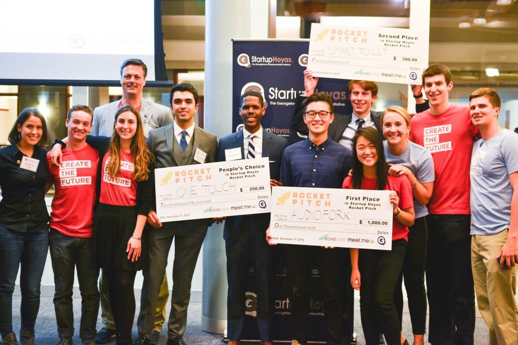 "Picture of students holding ""Startup Stipend"" program checks"