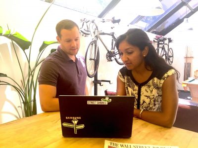 Picture of two students looking at a computer together with two bicycles in the background
